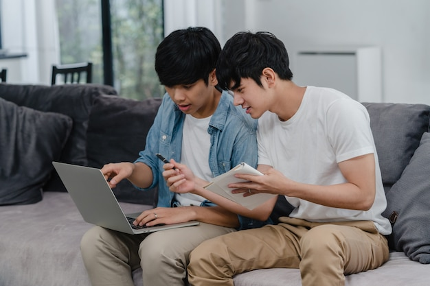 Young asian gay couple working laptop at modern home. asia lgbtq+ men happy relax fun using computer and analyzing their finances in internet together while lying sofa in living room at house . Free Photo