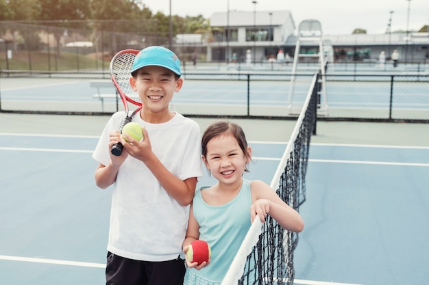 Young asian girl and boy tennis player on outdoor blue court Premium Photo