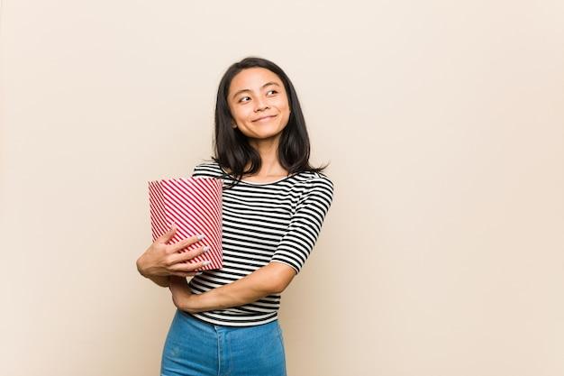 Молодая азиатская девушка держит ведро попкорна, уверенно улыбаясь со скрещенными руками. Premium Фотографии