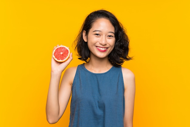 Young asian girl holding a grapefruit over isolated orange wall smiling a lot Premium Photo