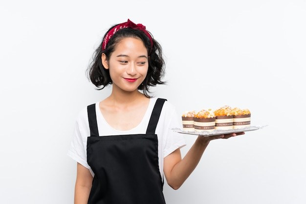 Young asian girl holding lots of muffin cake over isolated white wall with happy expression Premium Photo