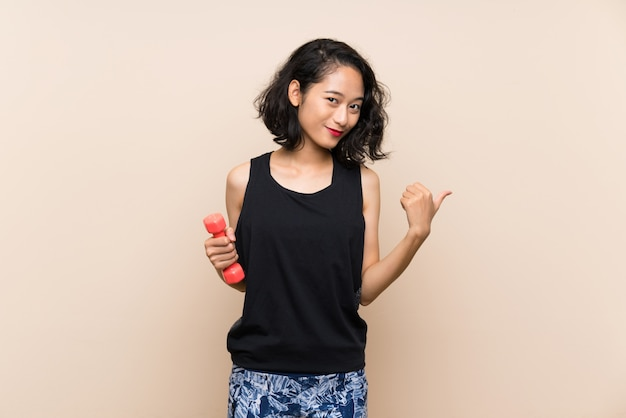 Young asian girl making weightlifting over isolated wall pointing to the side to present a product Premium Photo