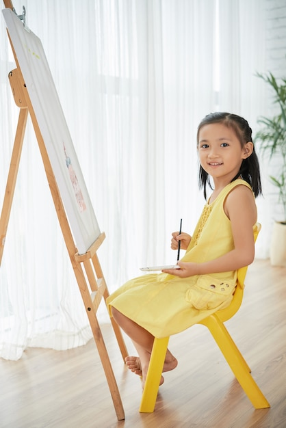 Young asian girl posing at home in front of easel, with painting brush and watercolors Free Photo