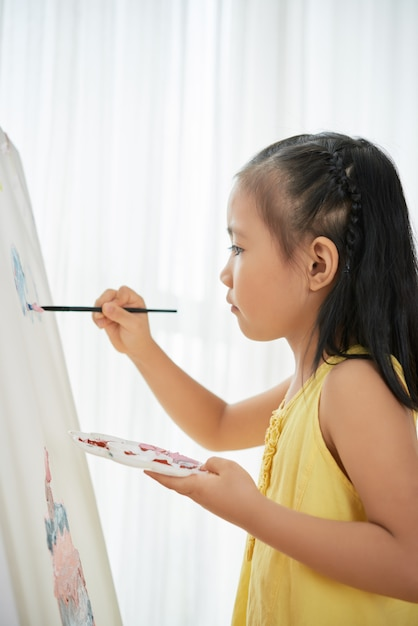 Young asian girl standing indoors in front of easel and painting picture Free Photo