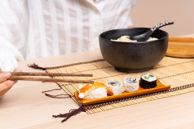 Young asian girl in a table with bowl of noodles and sushi Premium Photo