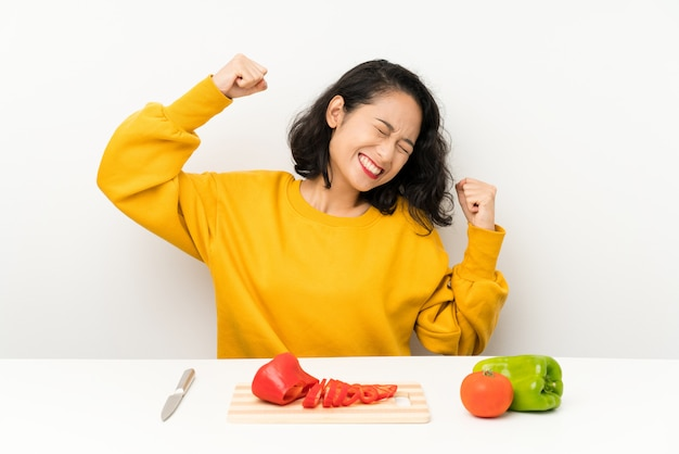 Young asian girl with vegetables in a table celebrating a victory Premium Photo