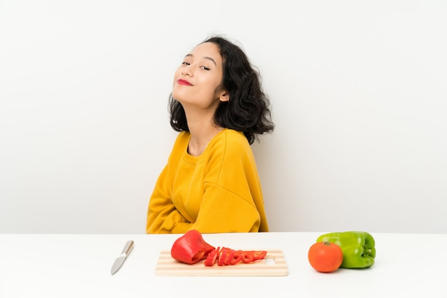 Young asian girl with vegetables in a table laughing Premium Photo