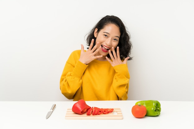 Young asian girl with vegetables in a table with surprise facial expression Premium Photo
