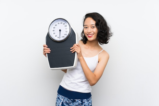 Young asian girl with weighing machine over isolated white wall Premium Photo