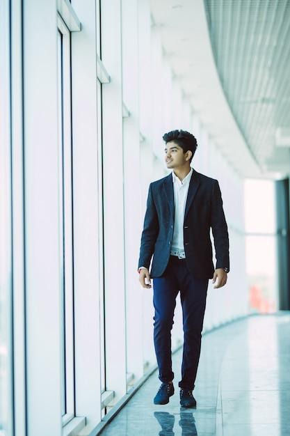 朝のオフィスに歩いて若いアジアインドのビジネスマン 無料写真