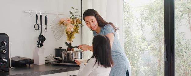젊은 아시아 일본 엄마와 딸 집에서 요리. 라이프 스타일 여성 아침에 집에서 현대 부엌에서 아침 식사를 위해 파스타와 스파게티를 함께 만드는 행복. 무료 사진