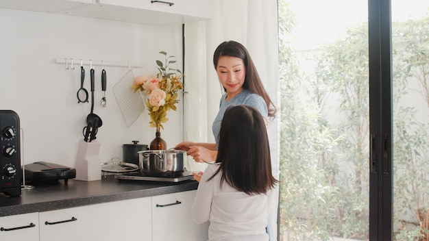 Young asian japanese mom and daughter cooking at home. lifestyle women happy making pasta and spaghetti together for breakfast meal in modern kitchen at house in the morning . Free Photo