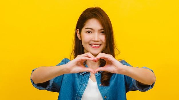 Молодая азиатская дама с положительным выражением, показывает жест руки в форме сердца, одетый в вскользь одежду и смотря камеру над желтой стеной. счастливая прелестная радостная женщина радуется успеху. Бесплатные Фотографии