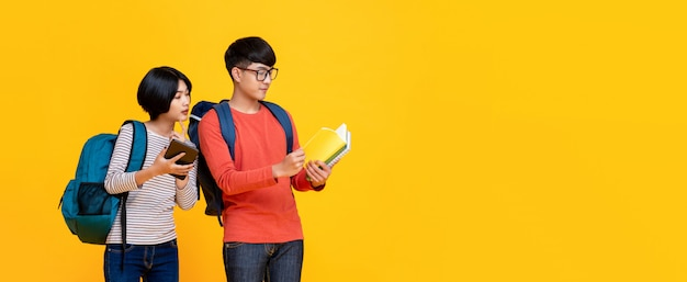 Young asian male and female students in colorful casual clothes looking at the book Premium Photo