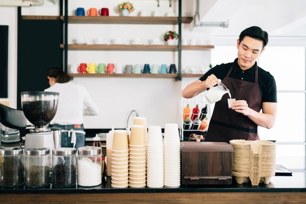Young asian male measuring milk for making latte coffee and female barista cafe owner standing inside the coffee counter. Premium Photo