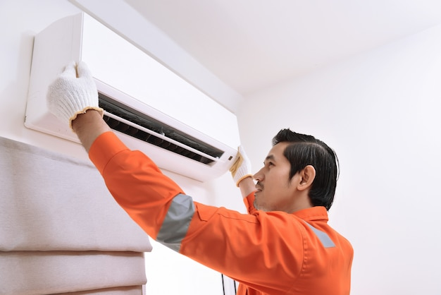 Young asian male technician repairing air conditioner Premium Photo