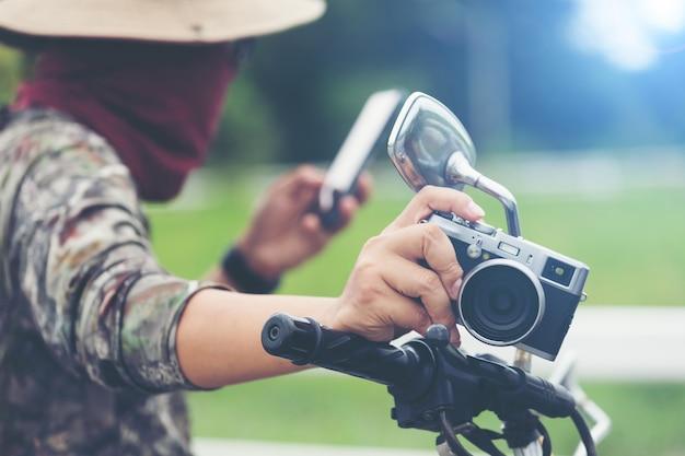 Молодой азиатский мужской путешественник и фотограф сидя на мотоцикле гонщика классического стиля держа камеру Бесплатные Фотографии