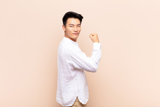 Premium Photo | Young asian man feeling happy, satisfied and powerful,  flexing fit and muscular biceps, looking strong after the gym over color  wall