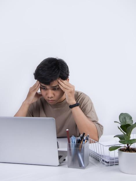 Молодой азиатский мужчина плохо себя чувствует в офисе, у него сильно болит голова от работы. студия выстрел, изолированные на белом фоне. Premium Фотографии