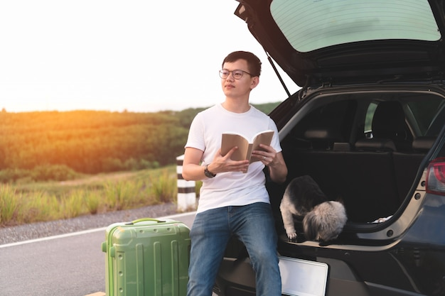 Young asian man holding book and looking at front while sitting in car open trunk with dogs. Premium Photo