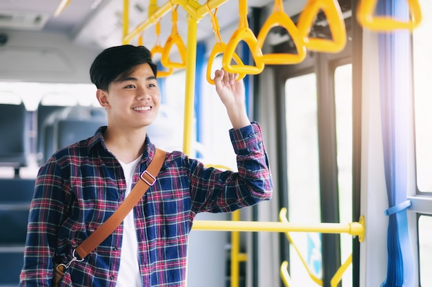 Premium Photo | Young asian man holding handle of the public bus.