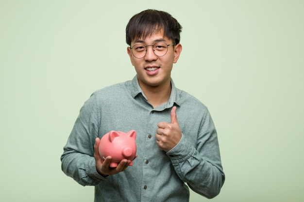 Young asian man holding a piggy bank smiling and raising thumb up Premium Photo