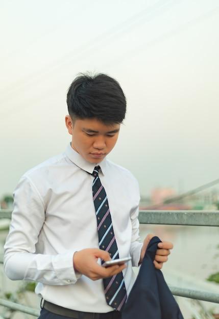 Молодой азиатский мужчина в костюме, отправляющий сообщение на его мед Бесплатные Фотографии