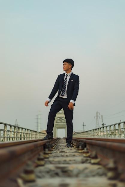 Молодой азиатский мужчина в костюме стоит посреди железной дороги, глядя в сторону Бесплатные Фотографии