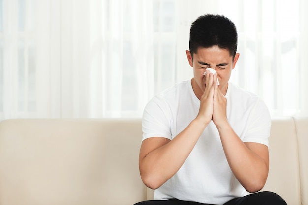 Young asian man sitting on couch at home and blowing nose with tissue Free Photo