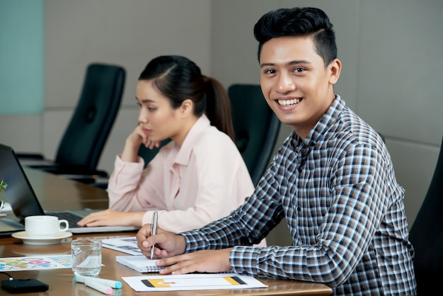 Young asian man sitting at meeting table in office and smiling, and woman working on laptop Free Photo