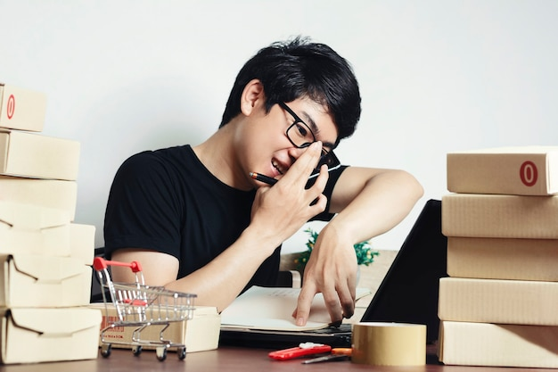Young asian man small business owner working at home office Premium Photo