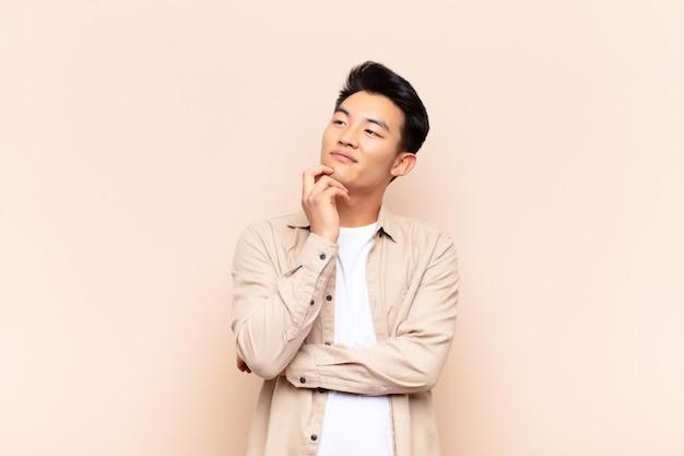Молодой азиатский человек улыбается счастливо и мечтать или сомневаться, глядя в сторону над цветной стеной Premium Фотографии