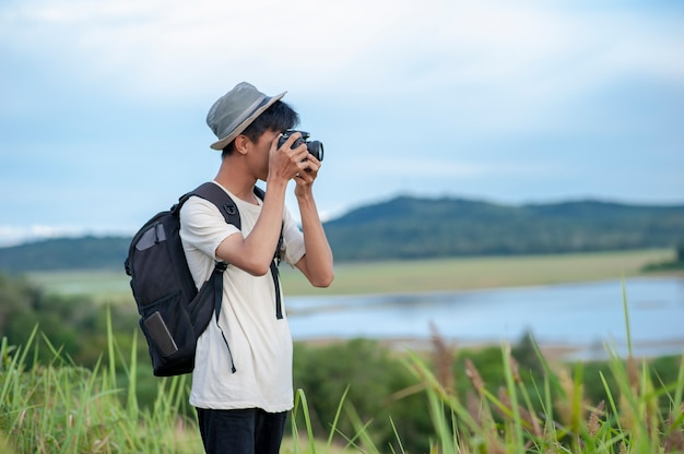 Young asian man traveler wearing knitted hat with backpack taking a photo and looking at amazing lake. Premium Photo