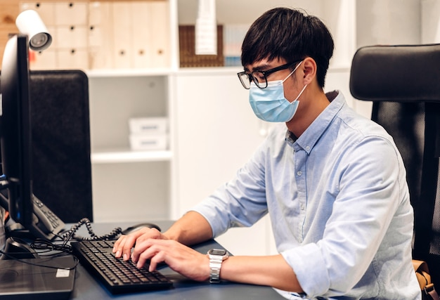 Молодой азиатский человек, использующий портативный компьютер, работает и видеоконференция, встречается в онлайн-чате в карантине для коронавируса, носит защитную маску с социальным дистанцированием дома. концепция работы из дома Premium Фотографии