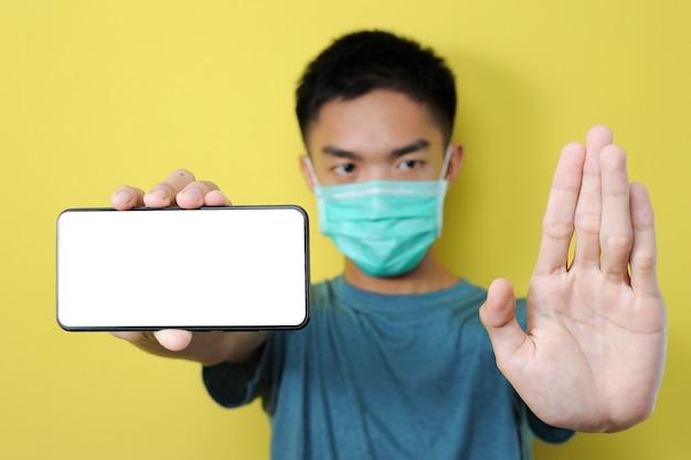 保護マスクを身に着けている若いアジア人男性が共有のデマ、偽のニュース、黄色に分離 Premium写真