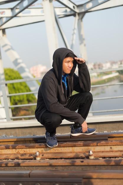 Молодой азиатский мужчина в куртке с капюшоном присел на железной дороге, глядя вдаль, положив руку на лоб Бесплатные Фотографии
