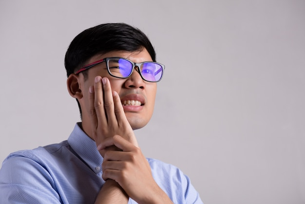 Young asian man with sensitive teeth or toothache. healthcare concept. Premium Photo