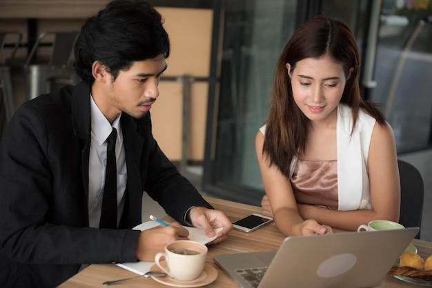 Young asian man and woman searching data on internet with laptop computer at cafe. Premium Photo
