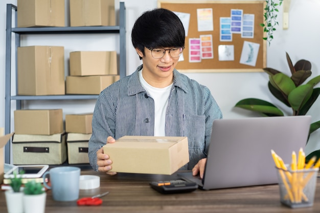 Young asian man working on delivery service office Premium Photo