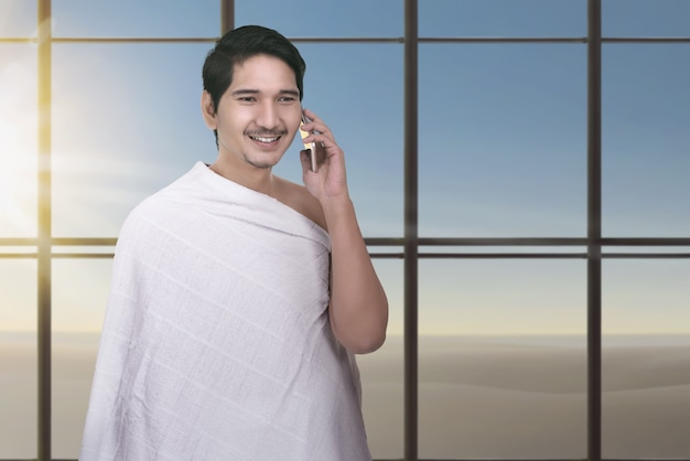 Young asian muslim man with ihram cloth using cellphone Premium Photo