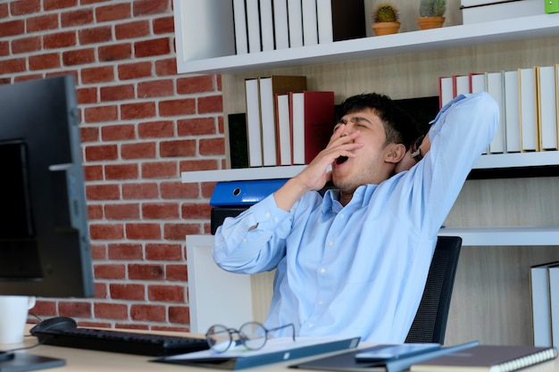 Young asian office man yawning while working on paperwork and computer Premium Photo