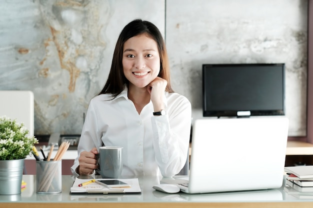 Young asian office woman working with laptop computer and holding coffee cup at desk office background, office lifestyle concept Premium Photo