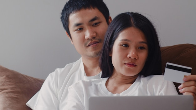 Young asian pregnant couple online shopping at home. mom and dad feeling happy using laptop technology and credit card buying baby product while lying on sofa in living room at home . Free Photo
