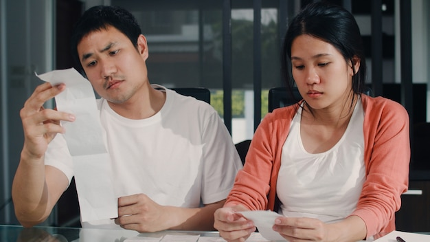 Young asian pregnant couple records of income and expenses at home. dad worried, serious, stress while record budget, tax, financial document working in living room at home . Free Photo