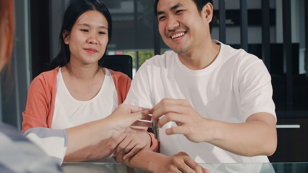 Young asian pregnant couple sign contract documents at home, japanese family consulting with real estate financial advisor, buying new house and handshaking with broker giving keys in living room. Free Photo