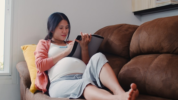 Young asian pregnant woman drawing baby in belly in notebook. mom feeling happy smiling positive and peaceful while take care child lying on sofa in living room at home . Free Photo
