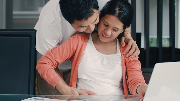 Young asian pregnant woman using laptop records of income and expenses at home. dad touch his wife belly while record budget, tax, financial document working in living room at home . Free Photo