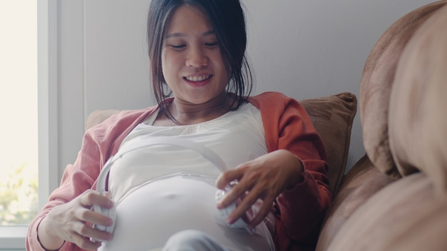 Young asian pregnant woman using phone and headphone play music for baby in belly. mom feeling happy smiling positive and peaceful while take care child lying on sofa in living room at home . Free Photo