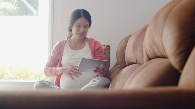 Young asian pregnant woman using tablet search pregnancy information. mom feeling happy smiling positive and peaceful while take care her child lying on sofa in living room at home . Free Photo