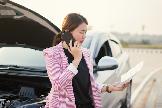 Young asian saleswoman  writing on clipboard with broken car Premium Photo